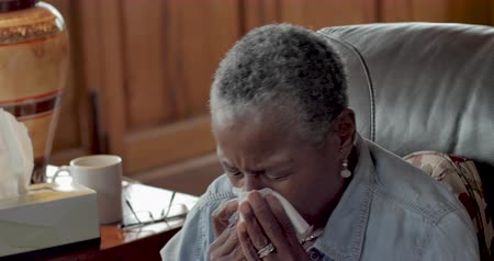 хмурый : Sick, elderly senior black woman in her 60s sneezing and using facial tissue to blow her nose with symptoms of a cold, flu, or allergies - close up Стоковые видеозаписи