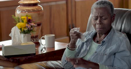 mračící : Sad, lonely, elderly black woman crying, wiping her eyes, and blowing her nose with facial tissue in her home