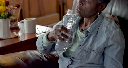 Elderly senior woman in her 50s or 60s drinking water from a single use recyclable plastic bottle