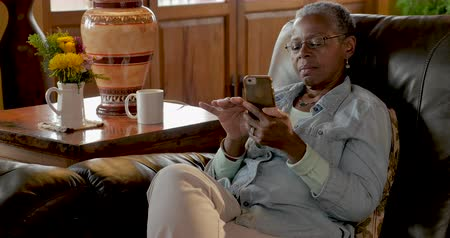 vertically : African American elderly senior woman in her 50s or 60s relaxing with her mobile phone reading and swiping while sitting on her living room couch during the day