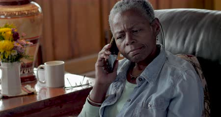 aborrecido : Annoyed senior black woman in her 50s or 60s answering her mobile phone and being bothered by the caller