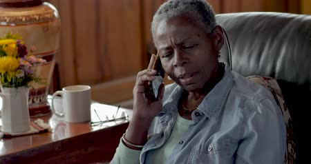 senki : Unhappy elderly senior black woman in her 50s or 60s talking on her mobile phone shaking her head no as if she is getting bad news