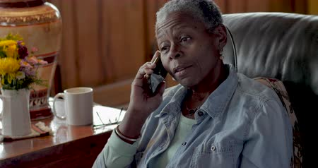 mračící : Frustrated, mad, senior black woman in her 50s or 60s talking on her mobile phone displeased at the annoying caller on the other end