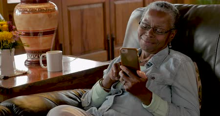 Happy smiling older senior black woman browsing, swiping and scrolling on her mobile phone while relaxing in her home
