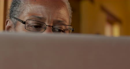 Dolly shot of an elderly black person wearing eyeglasses looking at a computer monitor in their home