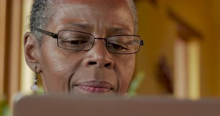 技术 : Elderly senior black woman in her 50s or 60s thinking and processing information while looking at a computer monitor - dolly shot