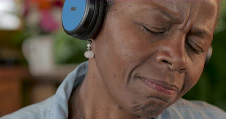 africký : Attractive African American senior woman listening to music with her eyes closed wearing wireless headphones and dancing back and forth
