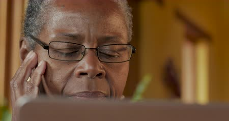фокус : Attractive elderly senior black woman in her 50s or 60s looking at her laptop computer screen - dolly shot