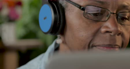 mladistvý : Senior black woman enjoying her music with headphones while looking at a digital display such as a laptop or digital tablet technology