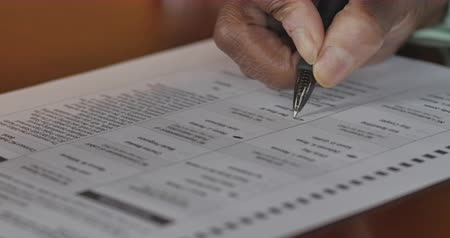 oy : Senior black hand voting on a voter paper ballot in an election