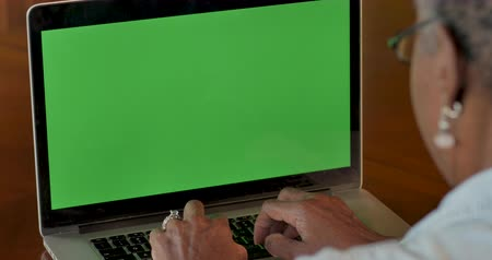 dizgi : Elderly senior black woman in her 50s or 60s typing on laptop with a green screen chroma key background - OTS