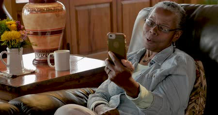 vertically : Happy smiling elderly senior black woman in her 50s or 60s video chatting on her mobile phone app technology Stock Footage