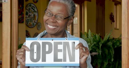 aperto cartello : Attractive black woman showing her open for business sign in front of her shop or gallery Filmati Stock