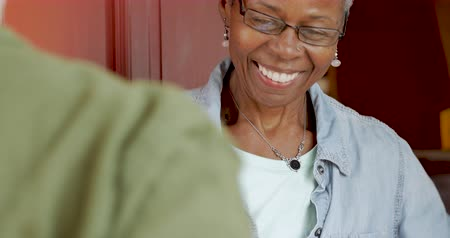 почтальон : Happy smiling senior black woman home owner receiving a delivery package from a postal courier and signing a digital proof of delivery signature