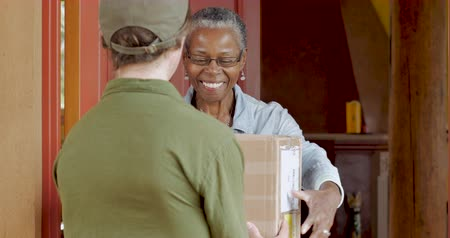 владелец : African American elderly woman receiving a home deliver package and digitally signing its proof of delivery from a postal courier man in a uniform