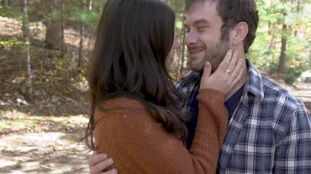 tarihleri : Young happy attractive couple in their 30s, kissing, hugging and showing affection in the woods with each other in slow motion Stok Video