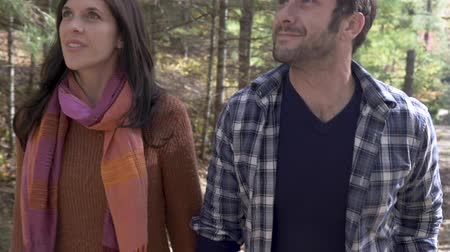 tarihleri : Attractive happy woman and man couple in their 30s holding hands and looking around at the forest while walking through a park trail in nature together in slow motion Stok Video