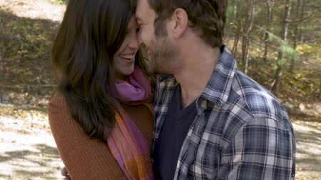 datas : Attractive couple in love kissing, laughing and hugging each other in a forest during the day in slow motion