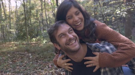 дата : Handsome happy man with a beard carrying a beautiful smiling attractive brunette woman on his back being playful outside in the woods in slow motion
