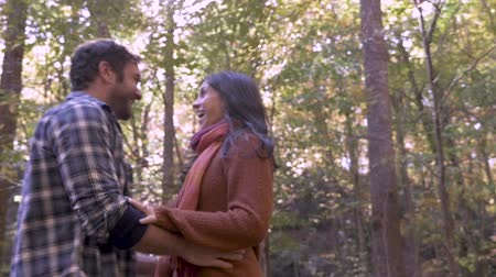 tarihleri : Attractive woman in her 30s throwing leaves on a handsome mans head during autumn while they are laughing and being affectionate- slow motion low angle with lens flare Stok Video