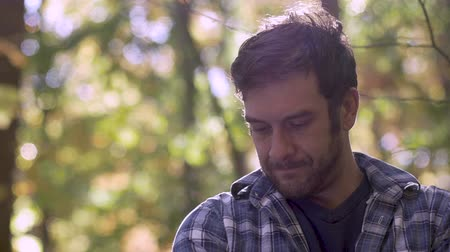 deli : Sad, frustrated handsome man thinking and looking down in the woods - slow motion low angle