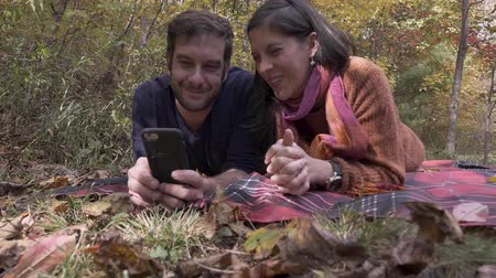 дата : Young happy smiling attractive couple in their 30s lying on a blanket looking at a smart phone together during the fall in a public park - slow motion