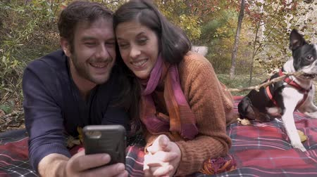 Бостон : Boston Terrier lies down next to a young happy attractive couple in their 30s taking a selfie together with their smart phone while lying on a blanket during the autumn - slow motion