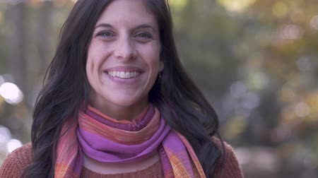 fidedigno : Portrait of a beautiful attractive caucasian brunette young woman in her 30s smiling and looking at the camera wearing a colorful scarf and sweater outside - slow motion Stock Footage