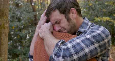 luto : Upset sad man hugging a woman after getting bad news or mourning the loss of someone while outdoors at a park Stock Footage