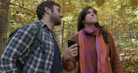 hiking : Frustrated young couple dependent on their mobile phone technology expressing anxiety, stress, and fear when they cant get cellular service while walking in the woods Stock Footage