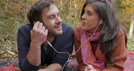 mężczyźni : Crane up of a happy smiling couple enjoying and listening to the same music together sharing the same earbuds or headphones outside while lying on a blanket in a park Wideo