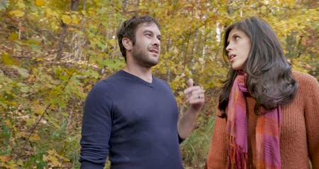 gritar : Arguing, frustrated young couple fighting and having a disagreement in a park or the woods during the fall