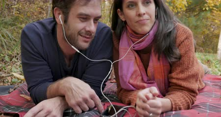 kulaklıklar : Happy young couple sharing the same music together with the same earbuds or headphones and talking while lying on a blanket outside - crane shot