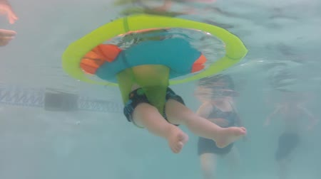 леди : an underwater shot of a baby in a flotation device with his family in a swimming pool.