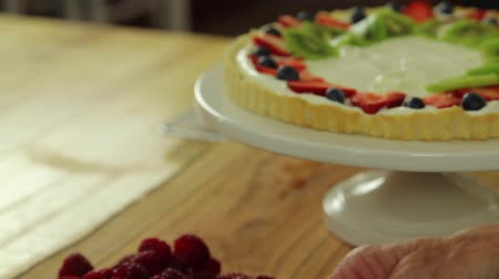 crust : woman making a delicious fruit tart with blueberries, raspberries, strawberries, and kiwi.