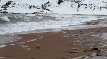 cape breton : a beautiful winter scene of a snow covered coast and rough ocean waters during a snow storm