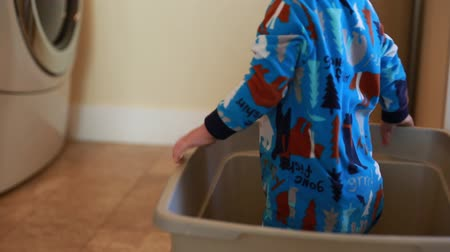 trabalhos domésticos : a little toddler playin in a laundry basket falls over and gets hurt