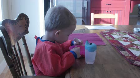 mísa : A little toddler boy eating granola cereal for breatkfast at the kitchen table