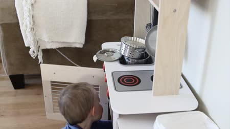 cozinhar : An adorable toddler playing with a toy kitchen set in his house
