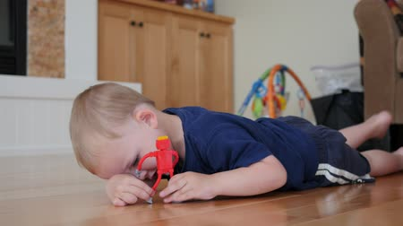 hazugság : A little boy lying on the floor of his home playing wity a pastic flexible toy robot Stock mozgókép