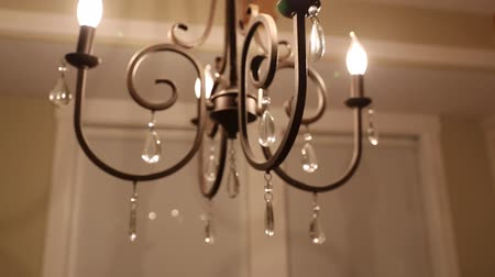żyrandol : a dolly shot of a beautiful chandelier in the home dining room