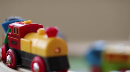 motor vehicle : a little boy plays with a toy train as it runs along the track