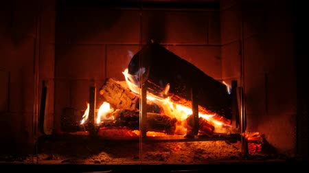 şömine : A wood burning fireplace at night in the living room of a house
