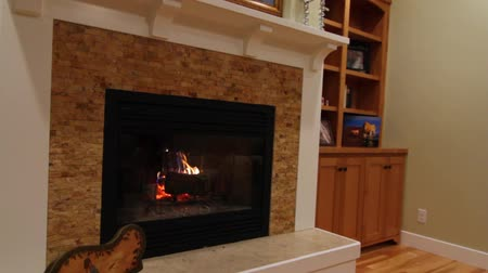 cozy : a jib shot of a cozy fireplace and mantle in a beautiful sitting room Stock Footage