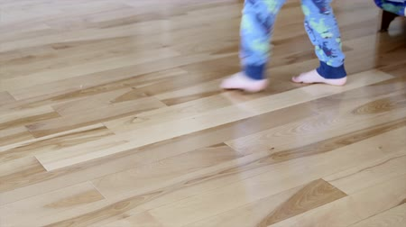 hazugság : A little boy twirls on a wood floor in his home staring at the camera