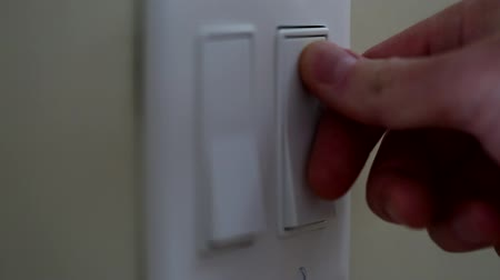 światło : a dolly shot of a hand turning on a light switch