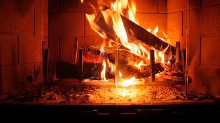helyek : A dolly shot of a wood burning fireplace at night in the living room of a house