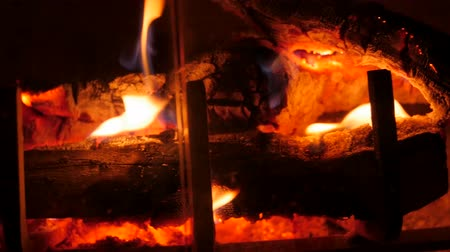 helyek : A jib shot of a wood burning fireplace at night in the living room of a house