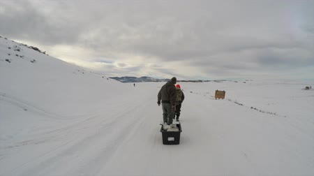 otcovství : a father and son walk toward a frozen lake to go ice fishing