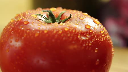 tomate : a woman puts a fresh tomato on the counter after rinsing it.